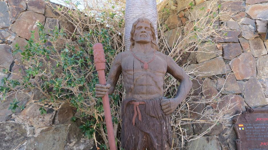 """Kuvassa ujjas guanchi nuija kädessään. Yhtä hyvin patsaan voisi tulkita esittävän muinaista """"Tahko Pihkalaa"""" joka pohdiskelee tulevan lajinsa ideologiaa."""