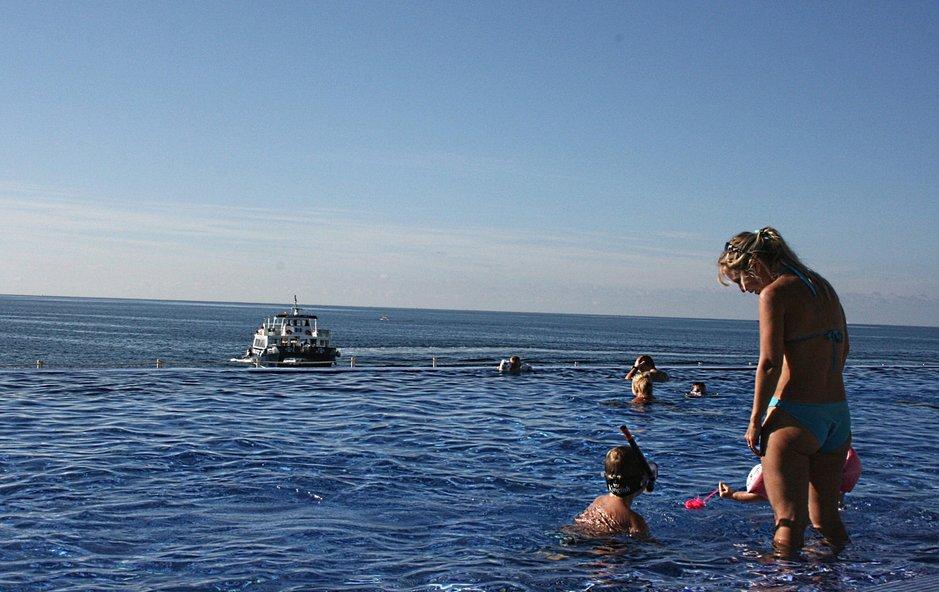 Lapsiperhe rentoutuu hotellin uima-altaalla Puerto Ricossa.