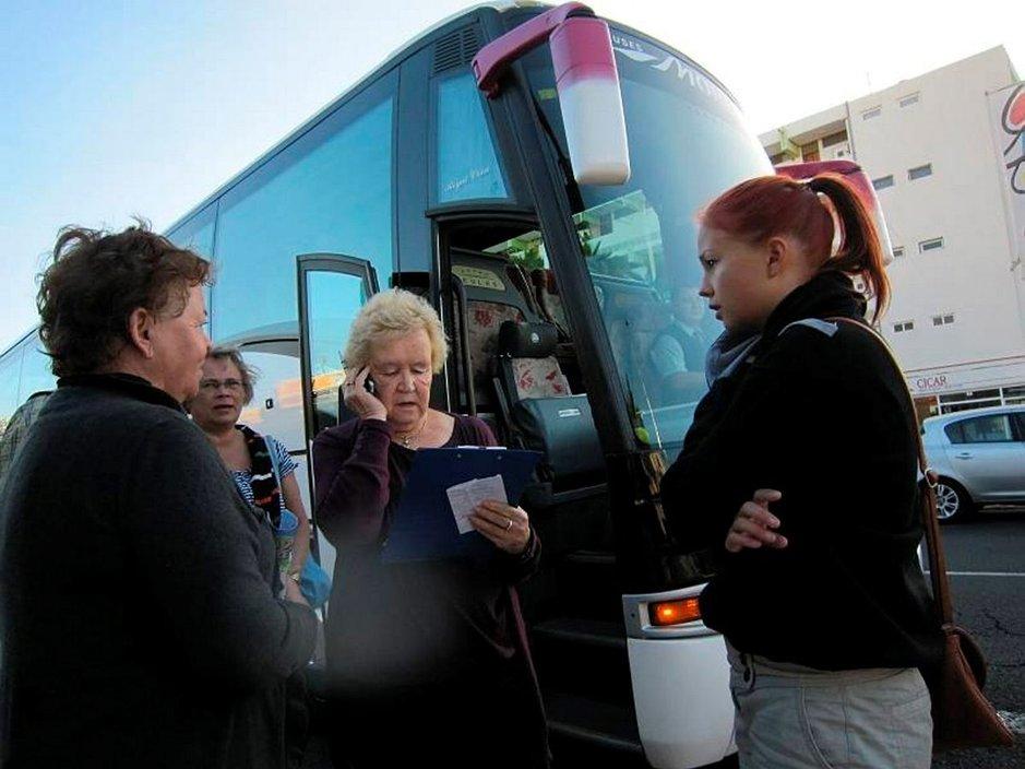Suomalaiset matkustavat omalla bussilla. Opas Marja-Leena Honkanen yrittää löytää istumapaikat myös niille, jotka eivät ole ilmoittautuneet ennakkoon.