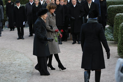 Presidentti Mauno Koiviston leski Tellervo Koivisto tyttärensä Assi Koiviston avustamana menossa laskemaan kaunista punaista ruusua muistopaadelle.