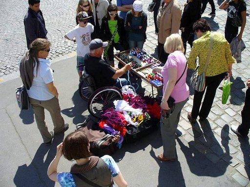 Pyörätuolissa istuva mies myy matkailijoille tekemiään avaimenperiä Montmartella.