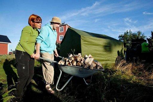 Susanna Tero ja Markus Rauhamäki vievät saunapuita telttasaunaan, jonka retkeläiset ovat pystyttäneet Ouraluodolle.