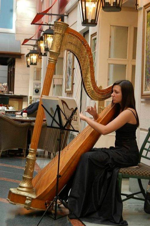 Harpputaiteilija soittaa joka päivä Grand Hotel Europen kahvilassa.