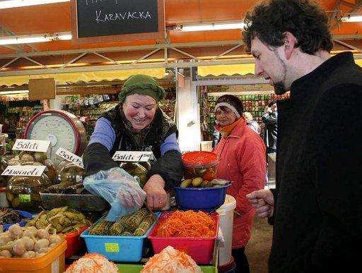 Riialainen Juris Berze ostaa kauppatorilta paikallista herkkua, marinoitua valkosipuliparsaa.