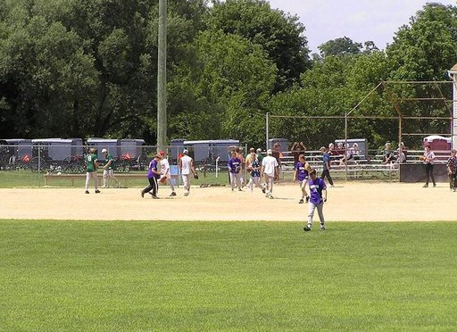 Baseball-ottelu mennoniitit vastaan amissit. Jälkimmäisiä ei vielä näy, mutta ajopelit ovat jo parkissa. Huomaa tyttöjen joukko aidalla.