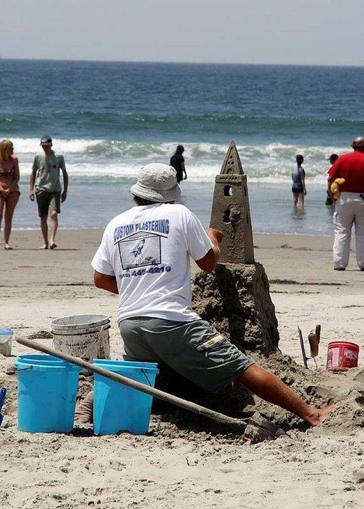 Rannalla harjoitellaan vuosittaisia hiekkalinnakilpailuja varten.