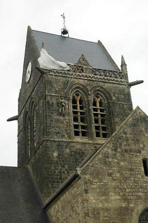 Sotamies John Steele riippumassa laskuvarjostaan kirkon tornissa. Hän haavoittui lievästi, mutta menetti kuulonsa, sillä kirkonkelloja soitettiin syttyneiden tulipalojen vuoksi.