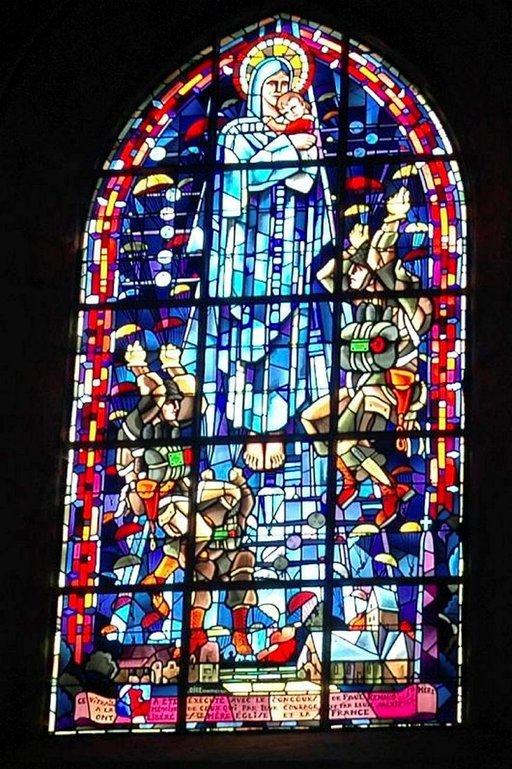 Poikkeuksellinen lasimaalaus Sainte-Mére-Église kirkossa. Taivaalta tulee laskuvarjojääkäreitä.