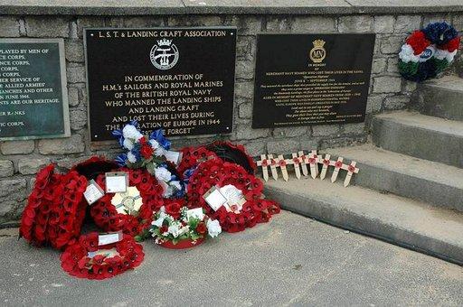 Kukkia, seppeleitä sekä puisia muistoristejä tuodaan edelleen muistomerkeille.