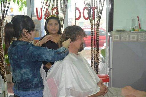 Taustalla oleva parturi aloitti hiusten leikkaamisen, mutta luovutti sitten työn rohkeammalle kollegalleen.