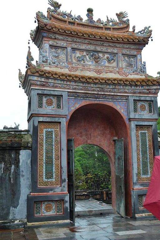 Tu Ducin mausoleumin sisäänkäynti tapahtuu jykevän portin kautta. Linnoituksen muurin rappaukset kaipaavat korjausta.