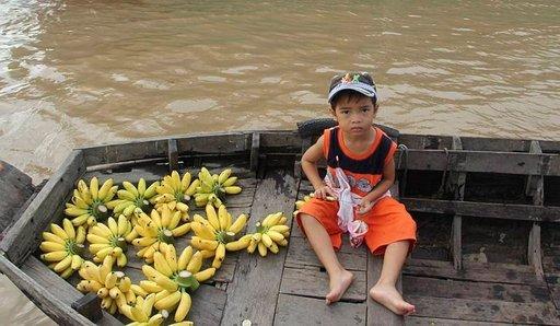 Pikkupoika Nguenilta voi ostaa kauniisti esille laitettuja banaaneja.