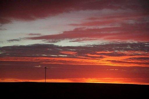 Aurinko nousee autiomaassa ja värjää taivaan huikeilla väreillä.