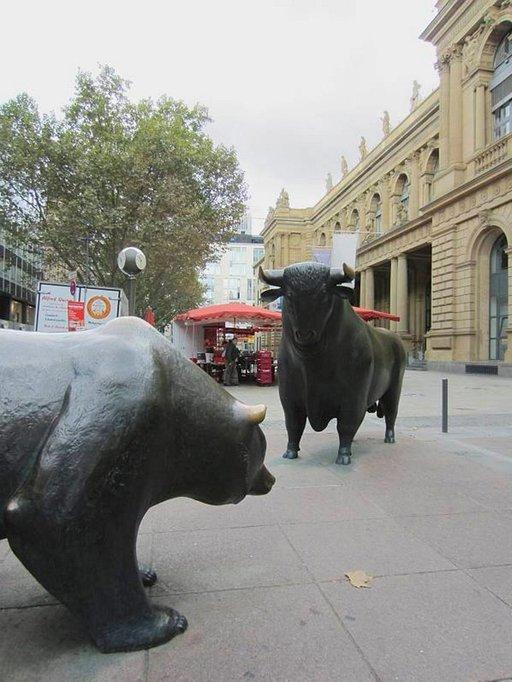 Härkä ja karhu käyvät tuijotuskilpailua pörssiaukiolla.