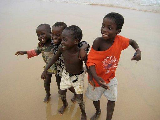 Lapset tanssivat azzontoa hiekkarannalla.