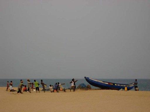 Kalastajat kiskovat venettä Ketan palmuista riisutulla rannalla.
