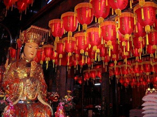Buddhalaistemppelien jumalankuvat ja värikkäät lyhdyt ovat väriläiskä muuten hiukan harmaassa kaupunkikuvassa.