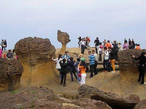 Mannerkiinalaisten matkailijoiden ryhmä ihastelemassa Taiwanin pohjoisrannikon erikoisia kalliomuodostelmia.