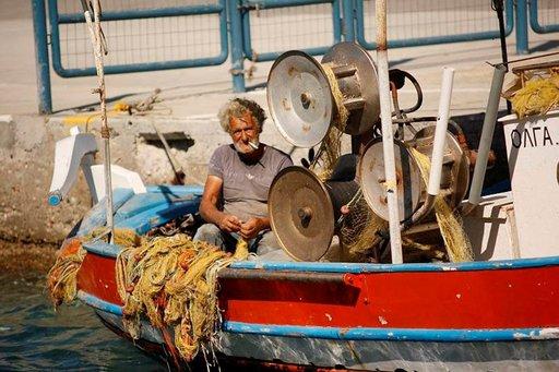 Aamuvarhainen kalareissu on takana. Kreikkalaisen kalastajan päivä kuluu välineitä kunnostamalla.