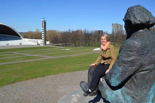 Gustav Ernesaksin patsas katselee laululavalle, kuoronjohtajan sylissä laulujuhlien kansainvälisistä asioista vastaava Maris Hellrand.