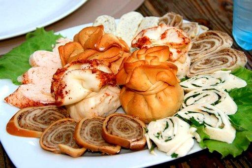 Georgialaiseen pitopöytään katetaan suolavedessä keitettyjä khinkalinyyttejä, joiden syömistekniikka on opeteltava isäntäväen auliilla avustuksella.