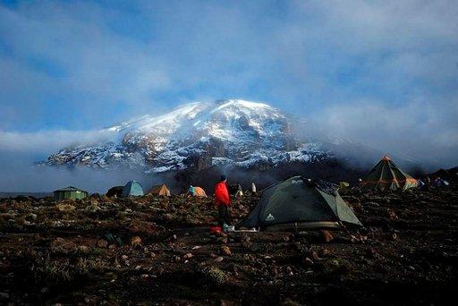 Oppaamme Alouise ihailee aamun valossa pilkistelevää Kilimanjaron huippua Karancan leirissä.