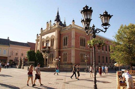 Rakennusten kauniit pastellivärit ja koristeelliset ikkunat hallitsevat näkymää Novi Sadin avarilla kävelykaduilla.