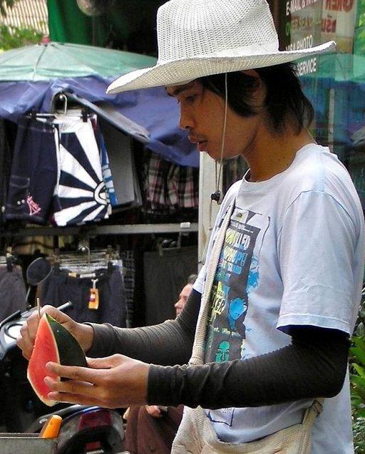 Hedelmäkauppias leikkaa vesimelonia Kowloonin kadulla.