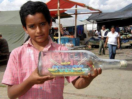 Markkinoilla pikkupoika kaupittelee pulloon tehtyä laivaa.