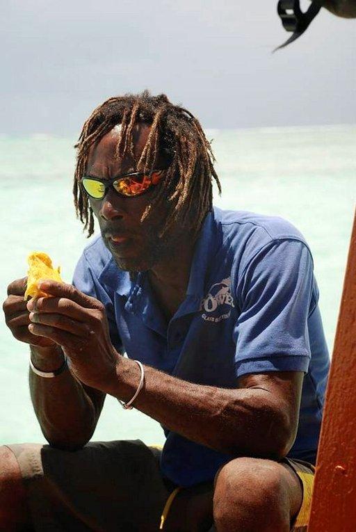 Lasipohjaveneen kapteeni Curtis haukkaa mangoa välipalaks