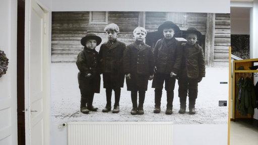 Lapualaispoikien pukukoodi 1930-luvulta. Valokuvasuurennos Wanhan Karhunmäen seinällä tervehtii Körttimuseoon saapuvia.