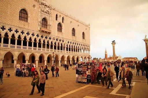 Ihmiset hakeutuvat suojaan sateelta Pyhän Markuksen torilla Venetsiassa.