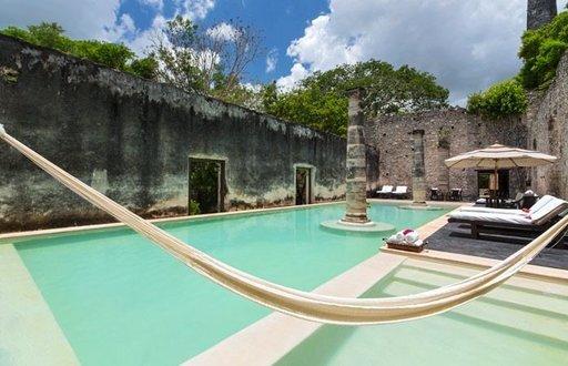 HACIENDA UAYAMON, CAMPECHE, MEKSIKO Hacienda Uayamonin altaalla voi polskia raunioissa. Kuva: Hacienda Uayamon a Luxury Collection Hotel - 1700-luvulla rakennettu Hacienda Uayamon on historiallinen boutique-hotelli vain puolen tunnin ajomatkan päässä Campechen kaupungista. Nimi hacienda viittaa maa- ja karjatilaan. Hotelli on samalla historiallinen kohde, jonka alkuperäisiä rakenteita ja sisustusta varjellaan aitouden säilyttämiseksi. Rehevän kasvillisuuden, iäkkäiden raunioiden ja nykyaikaisten mukavuuksien yhdistelmä luo romanttisen ilmapiirin, jota täydentää hotellin ainutlaatuinen uima-allas. Entisen konehuoneen raunioihin rakennetun pienen, mutta houkuttelevan altaan keskellä seisovat roomalaistyyliset pilarit. Aurinko valaisee katotonta allasta koko päivän aina aamun ensisäteistä iltahämärään.